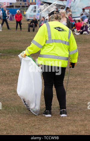 A litter picker in high visibility clothing picking up litter at a festival or outdoor event - Stock Image