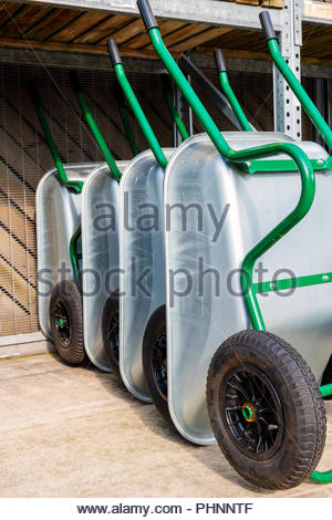 Wheelbarrows for sale at a garden centre, UK. - Stock Image