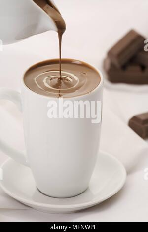 Drinking chocolate being poured into white porcelain cup. Chocolate in background. Studio shot.      Ref: CRB538_103609_0007  COMPULSORY CREDIT: Marti - Stock Image