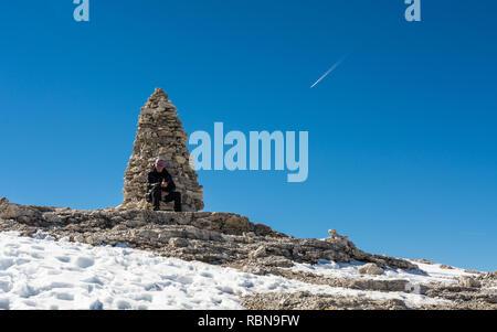 A tourist sitting near a pile of stones at the Sass Pordoi plateau, Dolomites, Trentino Alto Adige, northern Italy - Stock Image