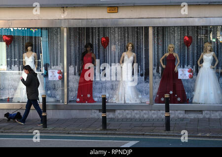 A woman walks past a wedding dress shop in Exeter, UK. - Stock Image