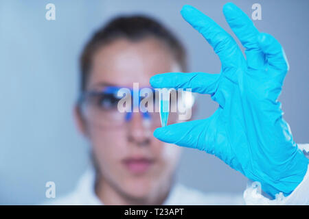 Young female scientist holding micro test tube. - Stock Image