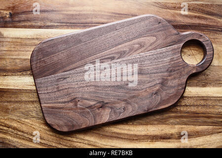 Walnut wooden cutting board with round handle hold over oak table top. Image shot from above in flat lay position. - Stock Image
