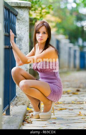Squatting girl teen teenager holding Blue metal fence small silky dress single nice outfit womans seductive great legs eyes-contact stilettos pumps - Stock Image