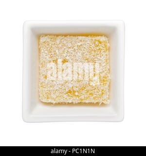Traditional Kueh Sago covered with coconut shreds in a square bowl isolated on white background; - Stock Image