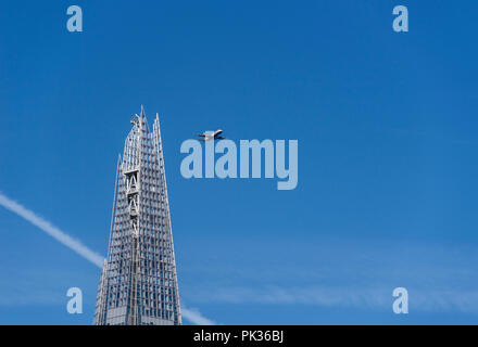 Low flying passenger plane close to the Shard on its final approach to landing at London City Airport, England, UK - Stock Image