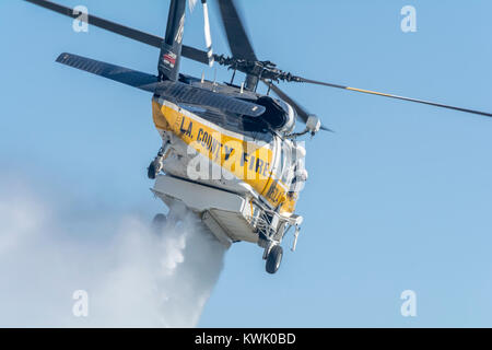 Los Angeles County Fire helicopter doing a water drop on a brush fire. - Stock Image