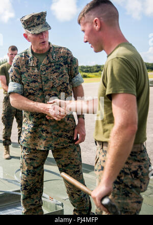 U.S. Marine Corps Lt.Gen. Mark A. Brilakis speaks to a Marine with Marine Wing Support Squadron 272 during his visitation on Marine Corps Auxiliary Landing Field Bogue, August 28, 2018. Lt.Gen. Brilakis visited the 2nd Marine Aircraft Wing (2d MAW) in order to orient himself on the current status of 2d Maw. Brilakis is the commanding general of Marine Forces Command. - Stock Image