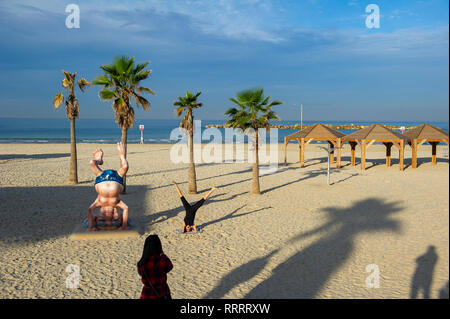 Young woman taking a picture of her friend doing yoga next to the Ben Gurion statue on the beach in Tel Aviv, Israel - Stock Image