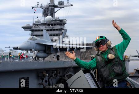 A Sailor prepares to launch Super Hornet aboard USS Carl Vinson. - Stock Image