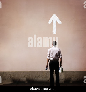 man with arrow painted on the wall - Stock Image