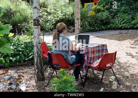 Lady on laptop outdoors, Dalston Eastern curve Garden, London Borough of Hackney. England, UK - Stock Image
