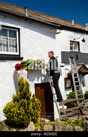 UK, Cumbria, Hawkshead, The Square, dressing the Kings Arms Hotel with floral planters in early summer - Stock Image