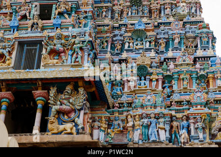 Painted statues on one of the gopura (towers) of Dravidian-style Kallalagar Temple, Madurai District, Tamil Nadu, India. - Stock Image