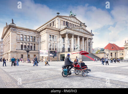 22 September 2018: Berlin Germany - Sightseeing in Gendarmenmarkt, with the Konzerthaus and a rickshaw or bike taxi. Slight motion blur on bike at 100 - Stock Image