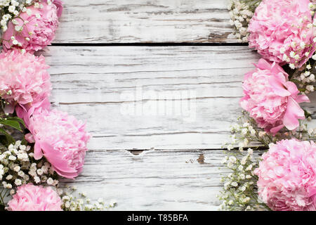 Pink Peonies and Baby's Breath flowers over a white rustic wood table background  with copy space for your text. Flat lay. - Stock Image