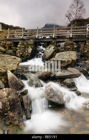 Rustic bridge over a mountain cascade at Cwm Idwal in the Glyderau range of mountains in Snowdonia National Park North Wales - Stock Image