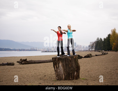 Two young women doing yoga at Spanish Bank Beach in Vancouver, British Columbia, Canada - Stock Image
