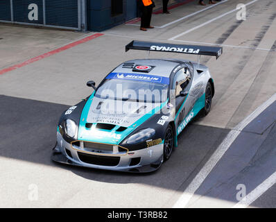 Looking down on a 2005, Silver Aston Martin DBRS9 GT3,  exiting the pit lane during the 2019 Silverstone Classic Media Day. - Stock Image