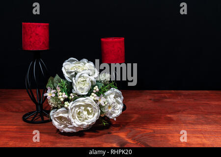 Beautiful bouquet of arranged flowers red candles on a holder on a wooden table. mothers day, Easter, valentines, birthday, Christmas, - Stock Image