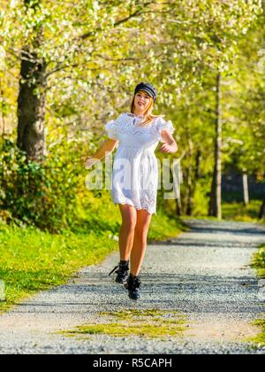 Adolescent teenager girl pretty natural in nature jumping running on countryroad against camera smiling happy fast - Stock Image