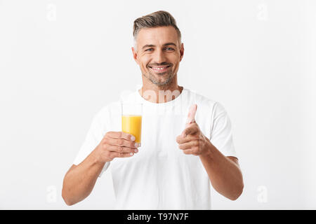 Image of cheerful man 30s with bristle wearing casual t-shirt holding glass of orange juice isolated over white background - Stock Image