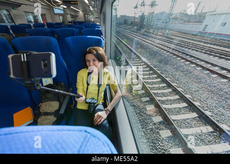 Young woman making selfies with smartphone during traveling in train sitting near window wideangle portrait - Stock Image