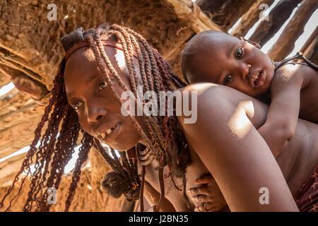 Africa, Namibia, Opuwo. Himba mother carrying child on her back. Credit as: Wendy Kaveney / Jaynes Gallery / DanitaDelimont.com - Stock Image