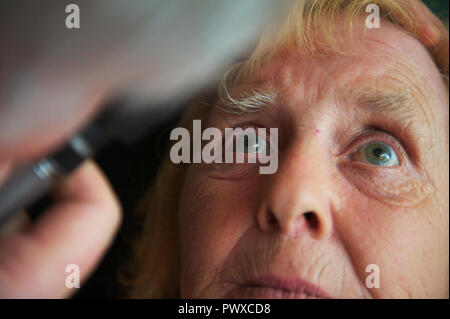 elderly female patient stares at doctors or GP eye examination light during appointment at GP surgery or community visit - Stock Image