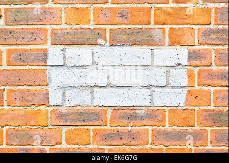 Patch of grey paint on a brick wall - Stock Image