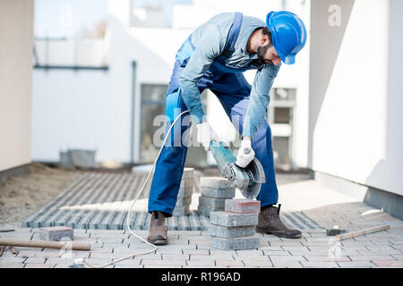 Builder in uniform cutting paving tiles with electric cutter on the construction site with white houses on the background - Stock Image
