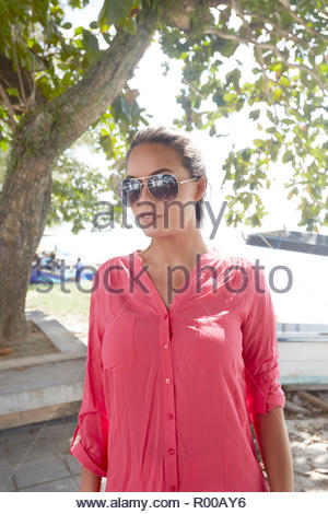 Young woman wearing sunglasses and pink button down shirt - Stock Image