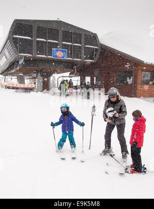 woman helping small children put on ski helmets before going skiing in front of a ski lift in heavy falling snow - Stock Image
