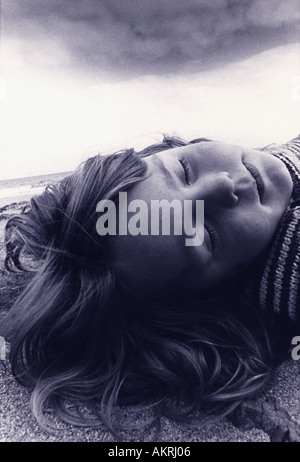 Girl asleep on beach - Stock Image