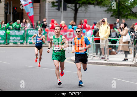 Declan Ryan (IRL),  with his guide runner, competing in the World Para 2019 London Marathon. Declan finished 16th in a time of  02:45:42 - Stock Image