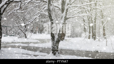 Winter park under the snow. Snowstorm in the city park. Park for walks with the whole family under the snow cover. - Stock Image