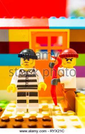 Poznan, Poland - March 14, 2019: Two Lego escaped prisoners trying to break in a house with a crowbar. - Stock Image