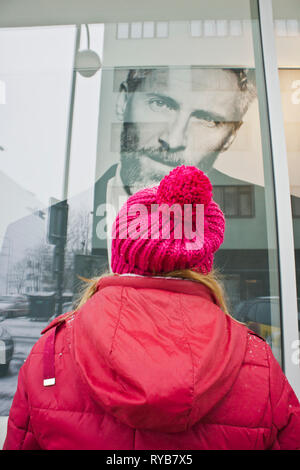 woman looking at and advert billboard with a handsome man face - Stock Image