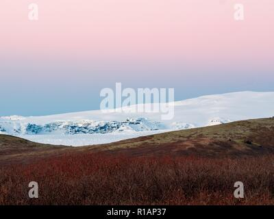 A pink sky above snow capped hills at sunrise in southern Iceland - Stock Image