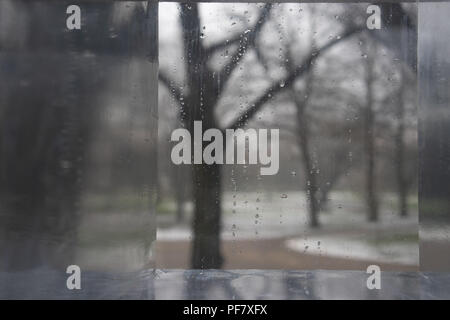 Winter park through a glass with drops - Stock Image
