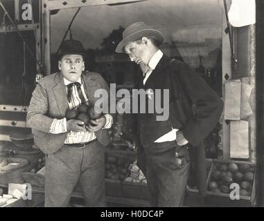 Sheriff catching man stealing from fruit stand - Stock Image