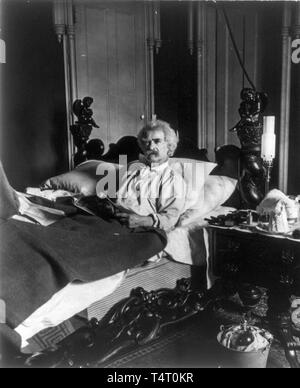 Mark Twain (1835-1910), lying in bed, holding magazine, 1906 - Stock Image
