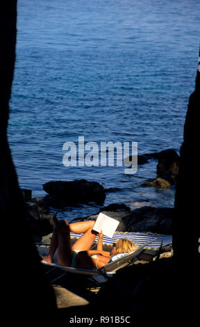 Woman laying on a deck chair in bathing costume reading a book, Bozava, Dugi Otok, Croatia - Stock Image
