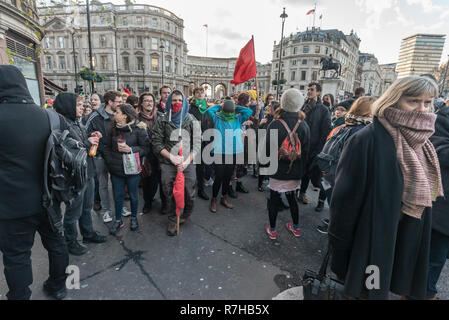 London, UK. 9th Dec, 2018. After stopping them for a few mintues, police escorted a large group of anti-fascists from Whitehall to disperse at Charing Cross station. They had taken part in the united counter demonstration by anti-fascists in opposition to Tommy Robinson's fascist pro-Brexit march. Police had issued conditions on both events designed to keep the two groups well apart. Credit: Peter Marshall/Alamy Live News - Stock Image