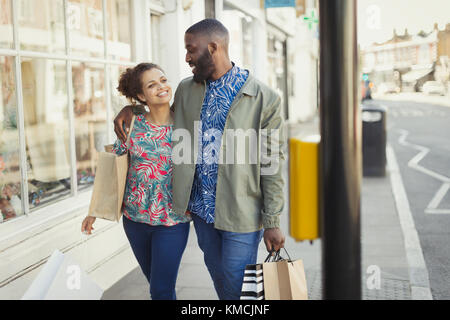 Affectionate young couple with shopping bags walking along urban storefront - Stock Image