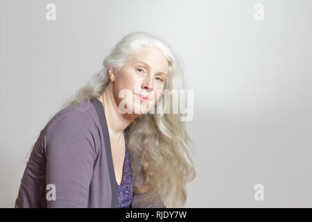 Portrait of an attractive mature woman with beautiful long gray hair in front of white background, copy space - Stock Image