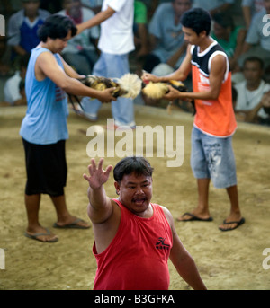 Filipinos place their bets before the start of a cockfight at a cockhouse near Mansalay, Oriental Mindoro, Philippines. - Stock Image