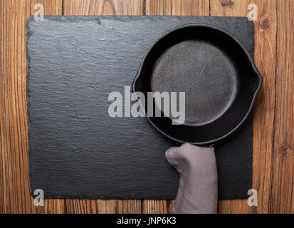 Empty cast-iron frying pan on black slate background (top view) - Stock Image
