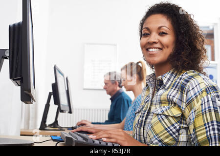 Portrait Of Young Woman Attending Computer Class In Front Of Screen - Stock Image