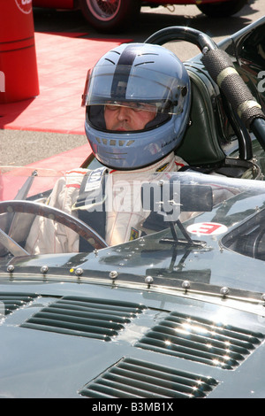 Racing driver in a classic racing car wearing a hemet on the start line at Silverstone - Stock Image